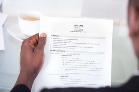 Close-up Of A Businessman Looking At Resume Holding In Hand photo