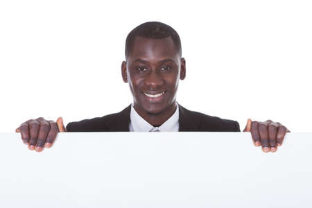 Portrait Of An African Businessman Presenting Blank Placard Over White Background photo