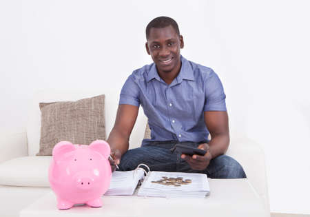 Happy African Man Sitting On Couch With Document And Piggybank photo