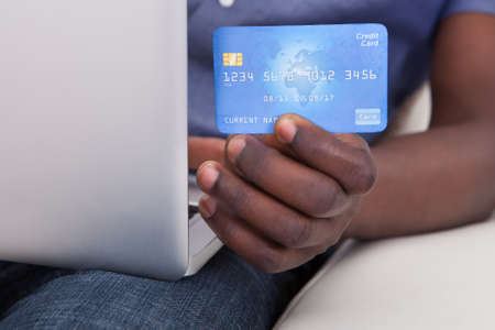 Close-up Of Hand Holding Laptop With Credit Card photo