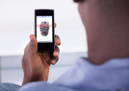 Person Holding Mobile Phone Showing Application With Process Of Scanning Fingerprint On A Screen photo