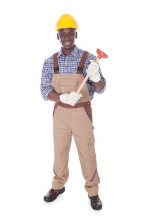Young Handyman Holding Plunger Over White Background photo