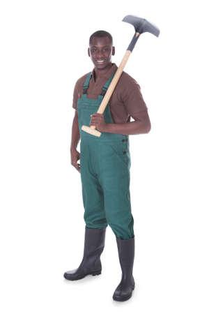 Male Gardener Holding Shovel Over White Background photo