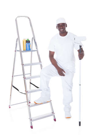 house robe: Young African Painter Holding Roller Over White Background Stock Photo