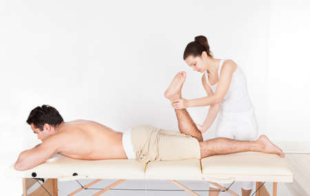 Young Man Lying On Table Getting Foot Massage From Masseuse Stock Photo - 25537742
