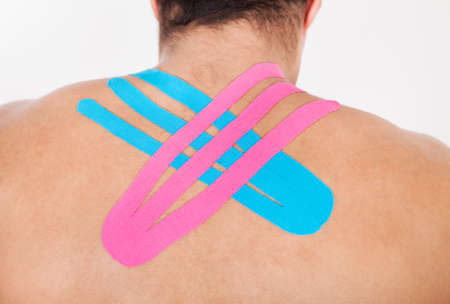 Rear View Of Young Man With Physio Tape Applied On Back photo