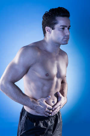 Portrait Of Young Shirtless Man Having Stomachache photo