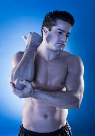 Close-up Of A Muscular Young Man Suffering From Elbow Pain photo