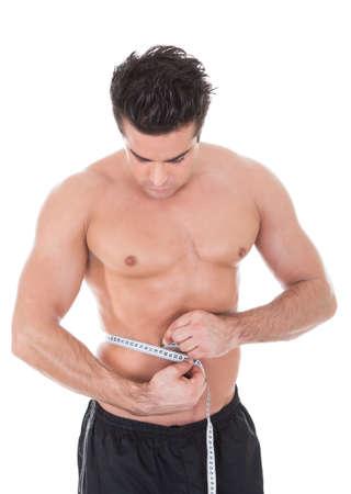 hombre flaco: Muscular Hombre joven descamisado Medir Su Cintura Foto de archivo