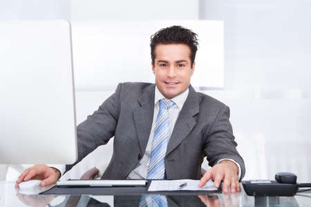 Portrait Of Young Businessman Using Computer At Office Stock Photo - 25538150