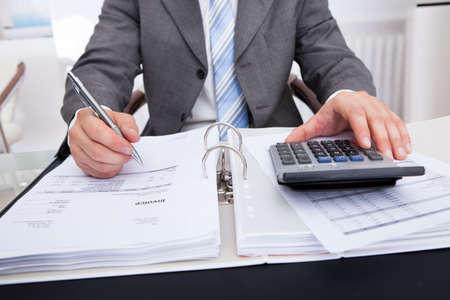 financial audit: Close-up Of A Businessman Calculating Bills Using Calculator