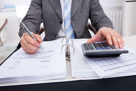 Primer plano de un empresario Cuentas calculadoras usando la calculadora