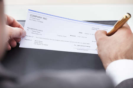 one dollar: Close-up Of A Businessman Filling Blank Cheque