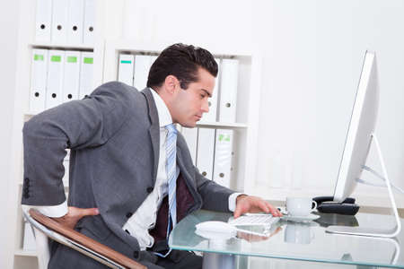 Young Businessman In Office At Desk Suffering From Back Pain photo