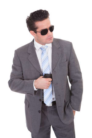Portrait Of Young Handsome Man With Black Sunglasses And Gun photo