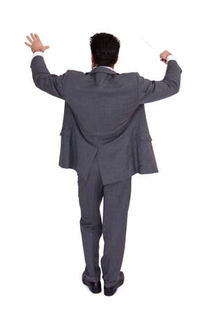 conductors: Rear View Of A Young Businessman Directing With A Conductors Baton Stock Photo