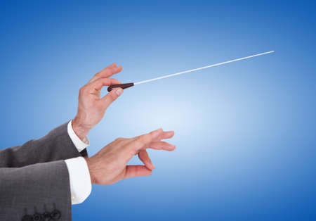conductors: Close-up Of A Person Directing With A Conductors Baton On Blue Background