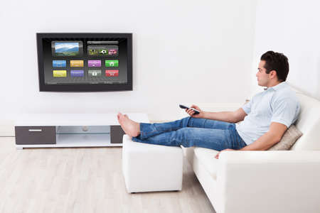 smart home: Young Man At Home Applying Setting Of Television Sitting On Couch