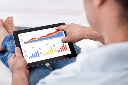 Close-up Man Analyzing Financial Statistics Displayed On The Tablet Screen photo