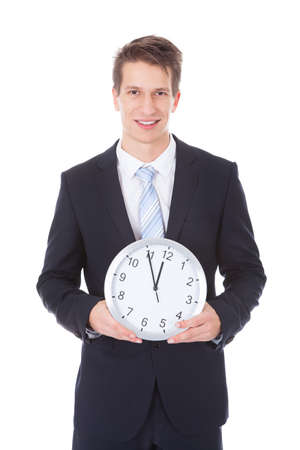 Portrait Of Young Businessman Holding Clock Over White Background photo