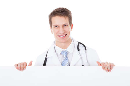 Young Male Doctor Holding Placard Over White Background photo