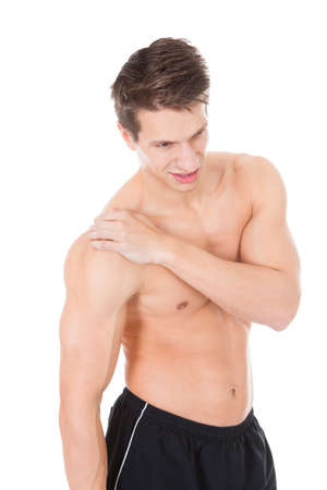 Portrait Of A Muscular Young Man Suffering From Shoulder Pain photo