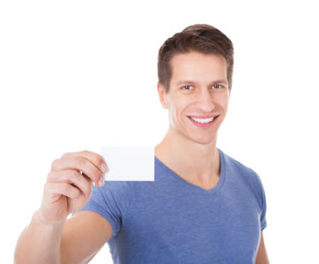 Portrait Of Young Man Showing Visiting Card Over White Background photo