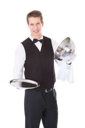 cloche: Happy Male Waiter Opening Cloche Lid Cover Over White Background Stock Photo