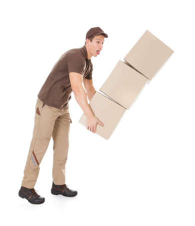 Young Delivery Man With Falling Stack Of Boxes Over White Background photo