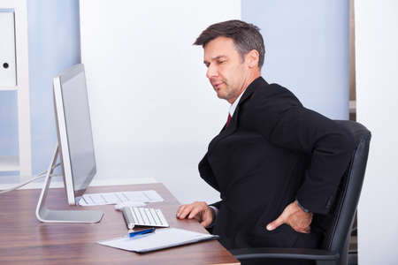 working stiff: Mature Businessman Suffering From Back Pain While Working In Office Stock Photo