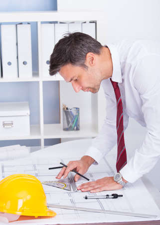 construction draftsman: Portrait Of Male Architect Drawing Blueprint In Office Stock Photo