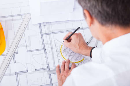 drawing table: Close-up Of Male Architect Drawing Blueprint In Office