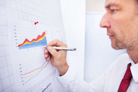 Close-up Of A Businessman Writing On Graph photo