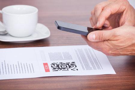 tomando refresco: Primer plano de una persona de escaneo de código de barras usando el teléfono celular
