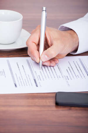 Close-up Of Businessman Writing On Paper With Pen photo