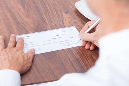 dinero falso: Llenar Mano Masculina el importe en un cheque