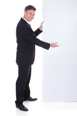 Portrait Of Mature Businessman Presenting Blank Placard photo
