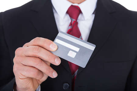 Close-up Of A Businessman In A Suit Holding Credit Card photo