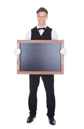 Portrait Of A Happy Smiling Waiter Holding Blank Chalkboard photo