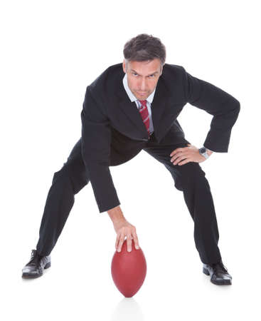 Portrait Of Mature Businessman Ready To Play American Football photo