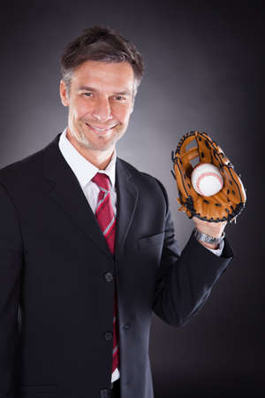 sportsperson: Happy Mature Businessman Holding Baseball And Mitt Over Black Background