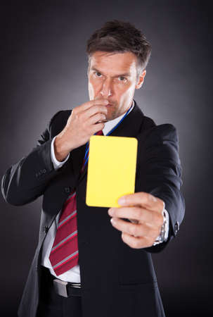 whistles: Portrait Of A Mature Businessman Showing Yellow Card Black Background