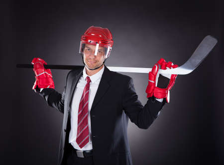 Portrait Of A Mature Businessman Dressed As Hockey Player Over Black Background Stock Photo
