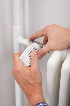Close-up Of A Male Plumber Adjusting Thermostat In Bathroom photo