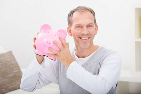 Portrait Of A Happy Mature Man Holding Piggybank photo