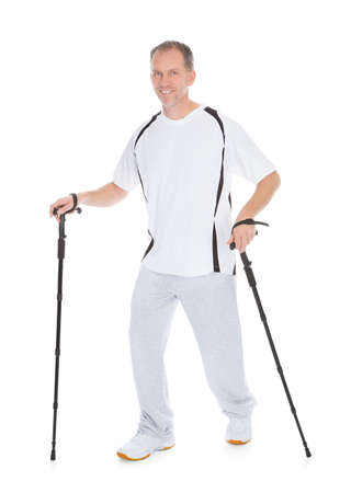 Portrait Of Man Walking With Hiking Pole Over White Background photo