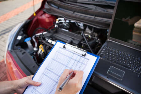 Male Mechanic Writing On Clipboard While Examining Car Engine photo