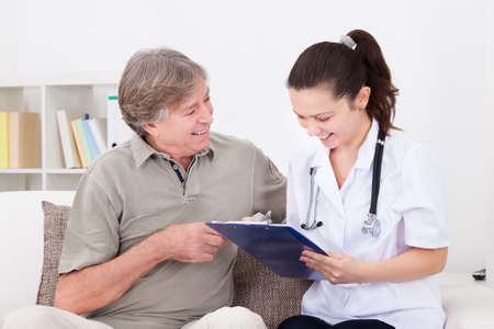 nurse clipboard: Happy Female Doctor Sitting With Patient On Couch Writing On Clipboard Stock Photo