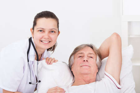 Young Female Doctor Consoling Senior Male Patient Lying On Bed photo
