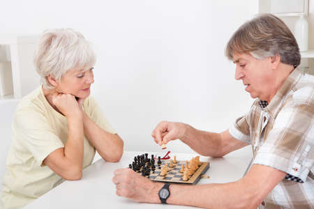 Senior Woman Playing Chess With Her Husband photo